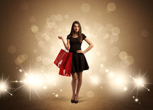 Shopping lady with bags in bright lights. A beautiful elegant woman in black standing with red shopping bags in front of brown background and bright glowing Royalty Free Stock Image