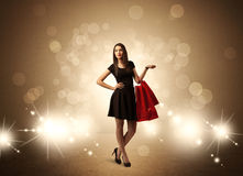 Shopping lady with bags in bright lights. A beautiful elegant woman in black standing with red shopping bags in front of brown background and bright glowing Stock Photo