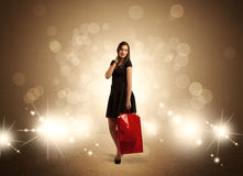 Shopping lady with bags in bright lights. A beautiful elegant woman in black standing with red shopping bags in front of brown background and bright glowing Stock Photos