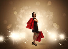 Shopping lady with bags in bright lights. A beautiful elegant woman in black standing with red shopping bags in front of brown background and bright glowing Royalty Free Stock Photo
