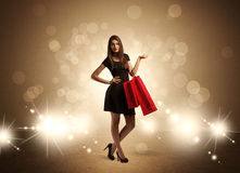 Shopping lady with bags in bright lights. A beautiful elegant woman in black standing with red shopping bags in front of brown background and bright glowing Stock Image