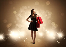 Shopping lady with bags in bright lights. A beautiful elegant woman in black standing with red shopping bags in front of brown background and bright glowing Stock Images