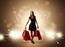 Shopping lady with bags in bright lights. A beautiful elegant woman in black standing with red shopping bags in front of brown background and bright glowing Stock Photography