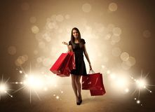 Shopping lady with bags in bright lights. A beautiful elegant woman in black standing with red shopping bags in front of brown background and bright glowing Royalty Free Stock Images