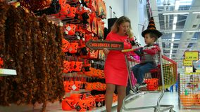 Shopping in a large supermarket on Halloween, mother and son preparing for All Hallows' Eve, Halloween Celebration. Sofia, Bulgaria - 15 September 2016: Shopping stock video footage