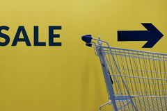 Shopping Lifestyle with Sale Promotional Concept. Empty Cart wit. H Text and Arrow Direction on the yellow Wall , ready for Customer to Pickup or Buying Products royalty free stock image
