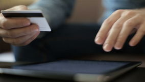 Shopping on-line with credit card on digital tablet stock video footage