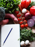 Shopping list. With a bunch of raw vegetables on table Stock Photos