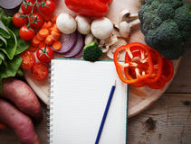 Shopping list. On table, with a bunch of vegetables Stock Photo