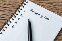 Shopping List, checklist to buy things from supermarket concept, pen with small notepad paper with handwriting headline as. Shopping List and numbers on wood royalty free stock image