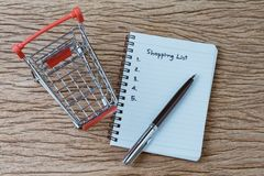 Shopping List, checklist to buy things from supermarket concept, pen with small notepad paper with handwriting headline as. Shopping List and numbers, miniature stock photos