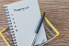 Shopping List, checklist to buy things from supermarket concept, pen with small note pad paper with handwriting headline as. Shopping List and number listed in royalty free stock images