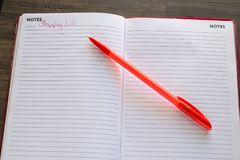 Shopping List with Red Pen Background. Shopping list on a gray wooden desk with white lined paper on notes page with a red pen useful for reminder concept Royalty Free Stock Photo