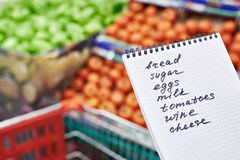 Shopping list in hand. Shopping list in the hands of a woman in a supermarket Royalty Free Stock Image