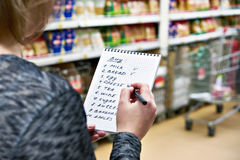 Shopping list in hands of woman in supermarket Royalty Free Stock Image