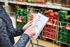 Shopping list in hands of woman in supermarket Stock Image