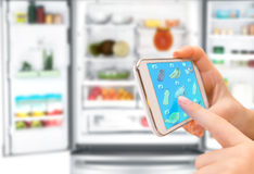 Shopping list on his phone connected to the refrigerator Stock Photo