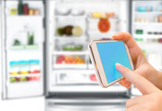Shopping list on his phone connected to the refrigerator Stock Images