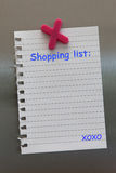 Shopping list note on a fridge door with magnet royalty free stock photo