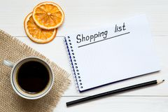 Shopping list on notepad on the white wooden table, copy space for your text royalty free stock photography