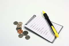 Shopping List, Pen, and Coins. A small note pad with a shopping list written on the open page, a pen, and a handful of pocket change Royalty Free Stock Images