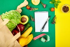 Shopping list, recipe book, diet plan. Grocering concept. Full paper bag of different fruits and vegetables, ingredients for stock images