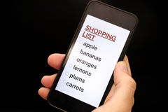 Shopping List on smart phone display in woman hand Royalty Free Stock Photo