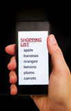 Shopping List on smart phone display in woman hand. With black background Royalty Free Stock Photo