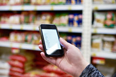 Shopping list on smartphone screen in hand of women customers Stock Photos