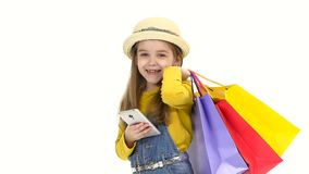 Shopping Little girl holding a mobile phone bags and looking at him and smiling. Slow motion stock video footage