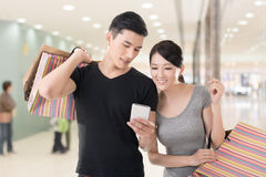 Shopping and looking at cellphone. Young Asian couple shopping and looking at cellphone, closeup portrait Stock Photography