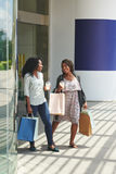 Shopping lovers. Cheerful women with paper-bags walking out of shopping mall Royalty Free Stock Images