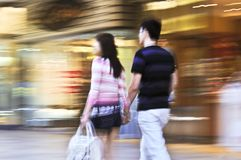 Shopping in a mall. Couple shopping in a mall, panning shot, intentional in-camera motion blur Stock Photo