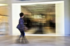 Shopping in a mall. Woman shopping in a mall, panning shot, intentional in-camera motion blur Stock Photos