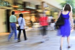 Shopping in a mall. People shopping in a mall, panning shot, intentional in-camera motion blur Royalty Free Stock Photography