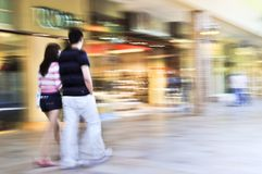 Shopping in a mall. Couple shopping in a mall, panning shot, intentional in-camera motion blur Royalty Free Stock Images