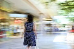 Shopping in a mall. Woman shopping in a mall, panning shot, intentional in-camera motion blur Royalty Free Stock Photography