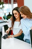 Shopping Mall. Girls Paying With Credit Card. Shopping Mall. Beautiful Girls In Stylish Clothes Paying With Credit Card At Store Checkout. High Resolution Stock Photo