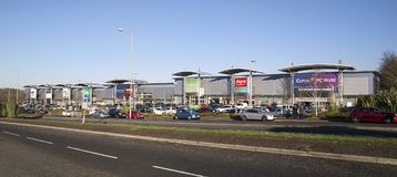 Shopping Mall Car Park with blue sky background in a panoramic format. Swansea, UK: December 28, 2016: Retail units including Argos, Currys and Marks and Spencer Royalty Free Stock Image