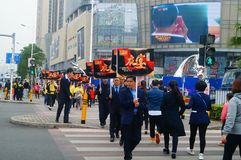 A contingent of billboards on the streets of Shenzhen. The shopping mall carries out a big sale of goods, and the staff of the market hold the billboard in the Stock Images
