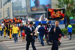 A contingent of billboards on the streets of Shenzhen. The shopping mall carries out a big sale of goods, and the staff of the market hold the billboard in the Royalty Free Stock Image