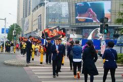 A contingent of billboards on the streets of Shenzhen. The shopping mall carries out a big sale of goods, and the staff of the market hold the billboard in the Stock Photos