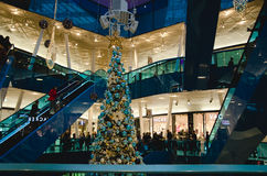 Shopping mall at christmas. Time with a big decorated Tree filled with gold and blue ornaments and people riding the escalator on a busy day royalty free stock images