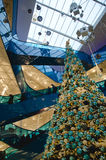 Shopping mall at christmas. Time with a big decorated Tree filled with gold and blue ornaments and people riding the escalator on a busy day stock photography