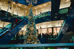 Shopping mall at christmas. Time with a big decorated Tree filled with gold and blue ornaments and people riding the escalator on a busy day stock photos