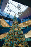 Shopping mall at christmas. Time with a big decorated Tree filled with gold and blue ornaments and people riding the escalator on a busy day stock image