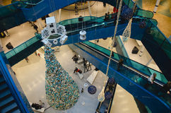 Shopping mall at christmas. Time with a big decorated Tree filled with gold and blue ornaments and people sitting, walking around and riding the escalator on a stock photo