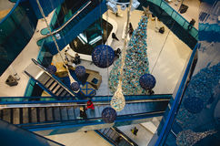 Shopping mall at christmas. Time with a big decorated Tree filled with gold and blue ornaments and people sitting, walking around and riding the escalator on a royalty free stock image
