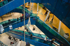 Shopping mall at christmas. Time with a big decorated Tree filled with gold and blue ornaments and people walking around and riding the escalator on a busy day royalty free stock photography