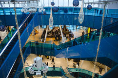 Shopping mall at christmas. Time with gold and blue ornaments and people walking around and riding the escalator on a busy day stock image